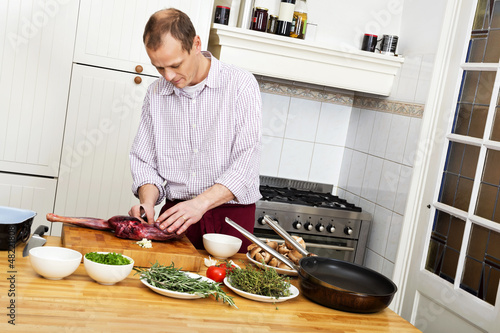 Man Preparing Meat In Kitchen