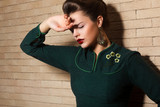 Aristocratic Brown Hair Sad Woman in Green Dress over Brick Wall