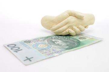 Splecione dłonie nad banknotem 100 zł