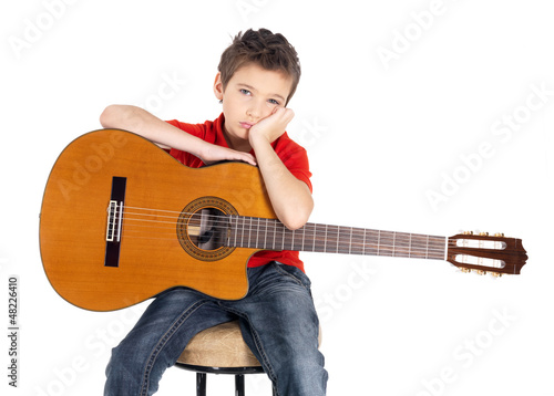 Sad white boy with a  acoustic guitar in his hands.