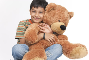 Indian boy holding teddy bear in indoors