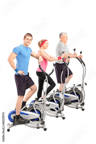 A studio shot of three people working on a cross train machine