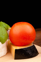 Various types of cheese and tomato on  black background