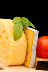 Various types of cheese and vegetables isolated on black