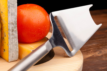 Various types of cheese,knife and tomato isolated on black
