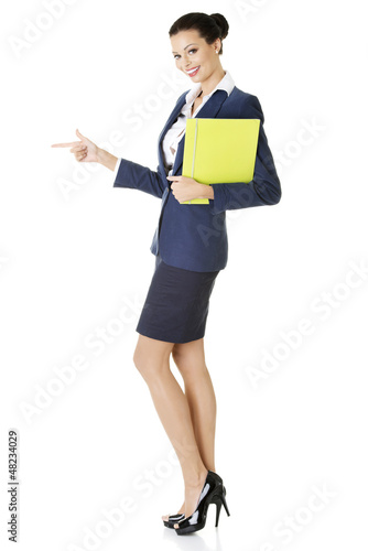 Success business woman pointing on copy space