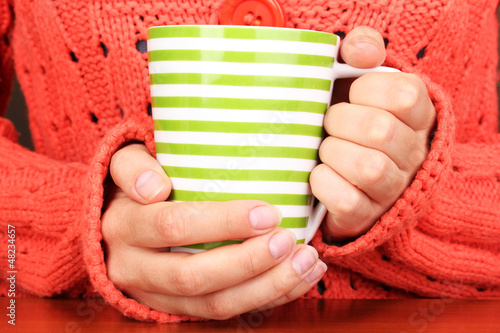 hands holding mug of hot drink close-up
