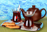 glass of Turkish tea and kettle on color background