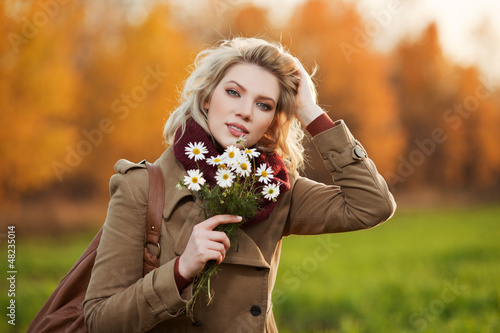 Young woman with a flowers in autumn field