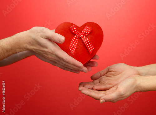 Red heart in woman and man hands, on red background
