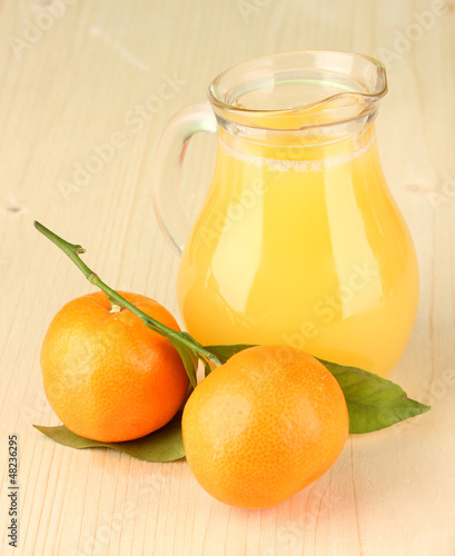 Full jug of orange juice, on wooden background