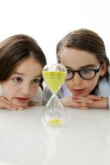 Kinder beobachten den Zeitablauf einer Sanduhr