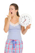 Young woman in pajamas with clock yawing after sleep