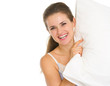 Smiling young woman looking out from pillow