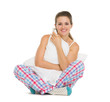 Smiling young woman in pajamas sitting with pillow