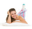 Smiling young woman in pajamas laying on pillow