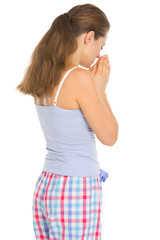 Young woman in pajamas praying before sleep. Rear view