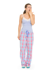 Young woman in pajamas yawing