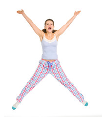 Smiling young woman in pajamas jumping