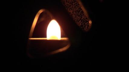 Candle burning in ceramic candleholder
