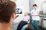 Dentist Examining X-Ray Image With Female Assistant Communicatin