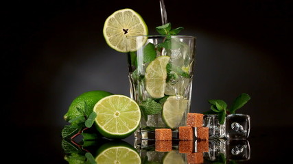 Pouring soda in mojito over dark background