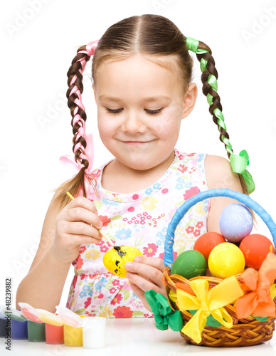 Little girl is painting eggs preparing for Easter