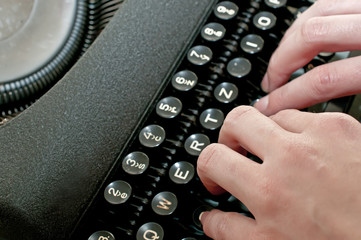 Hands are typing on vintage dirty typewriter