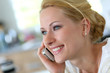 Attractive blond woman at home talking on mobilephone