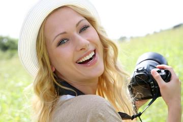 Portrait of adventure girl using photo camera in nature