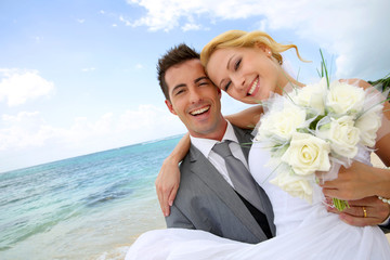 Groom holding bride in his arms at the beach