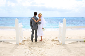 Just married couple standing by a fence towards this ocean