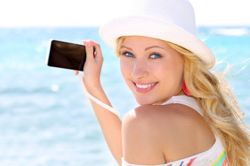 Cheerful girl talking pictures with digital camera