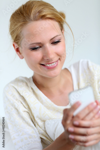 Portrait of blond girl using smartphone to send message