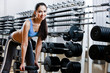 Strong woman chooses appropriate dumbbells in sport centre