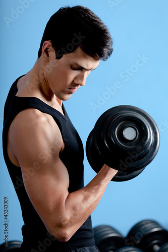 Handsome muscular athletic man uses his dumbbell