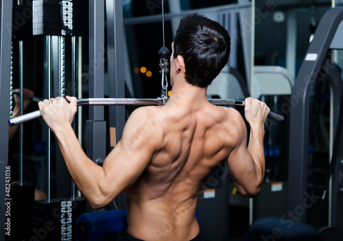 Athletic young man works out on training apparatus