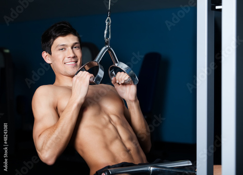 Athletic young man works out on training apparatus in gym