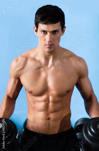 Handsome muscular man with sexy body uses his dumbbell
