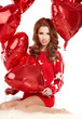 Beautiful fashion woman in red posing with red ballons