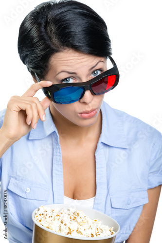 Girl in 3D spectacles watching movie with popcorn