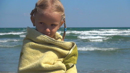 Child Trembling in a Towel after Bathing in the Sea