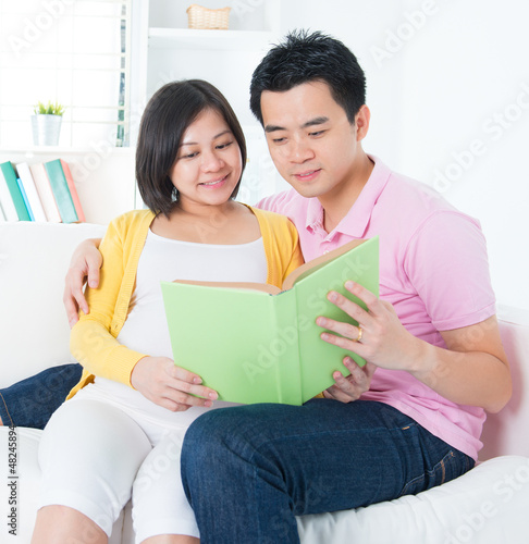 Asian couple reading book together