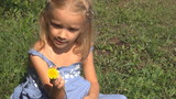 Little Girl Looking at a Dandelion, Child Playing with Flowers