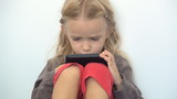 Little Girl Playing on the Touchscreen Phone