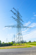electrical tower in field with street under blue sky
