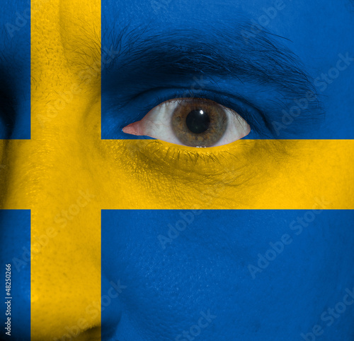 face with the Swedish flag painted on it