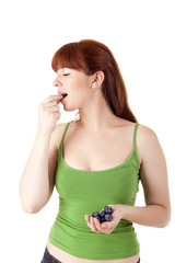 Beautiful woman eating blueberries
