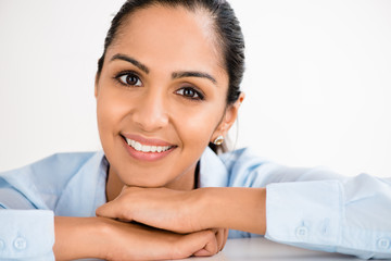 Closeup pretty Indian businesswoman smiling at desk in modern of