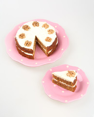 carrot cake with cream cheese frosting in a pink on white